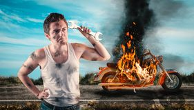 Needs help to repair the motorbike. Helpless man holding a wrench with his motorcycle on fire in the background. Needs help to repair the motorbike Royalty Free Stock Photo