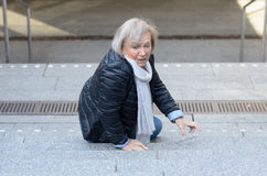Helpless senior woman falling down steps. And looking irritated Stock Image