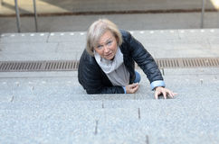 Helpless senior woman falling down steps. And looking upwards Stock Image