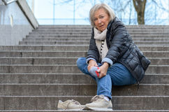 Helpless senior woman massaging her Foot. To relive aches and pains after falling down steps Stock Photos