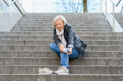 Helpless senior woman massaging her Foot. To relive aches and pains after falling down steps Stock Image