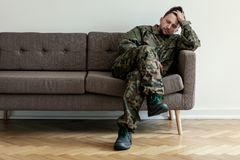 Helpless soldier sitting on a couch while waiting for a therapy session royalty free stock photo