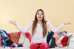 Helpless woman sitting on sofa in messy room home. Helpless woman sitting on sofa couch in messy living room shrugging. Young girl surrounded by many stack of Stock Photo