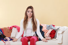 Helpless woman sitting on sofa in messy room home. Helpless woman sitting on sofa couch in messy living room shrugging. Young girl surrounded by many stack of Royalty Free Stock Images
