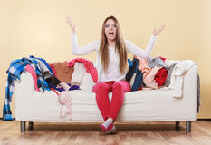 Helpless woman sitting on sofa in messy room home. Helpless woman sitting on sofa couch in messy living room shrugging. Young girl surrounded by many stack of stock photos