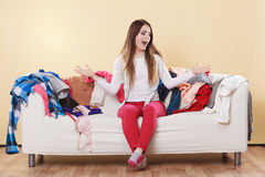 Helpless woman sitting on sofa in messy room home. Helpless woman sitting on sofa couch in messy living room shrugging. Young girl surrounded by many stack of Stock Image