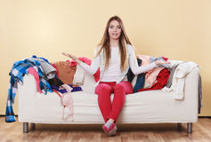 Helpless woman sitting on sofa in messy room home. Helpless woman sitting on sofa couch in messy living room shrugging. Young girl surrounded by many stack of Royalty Free Stock Photos