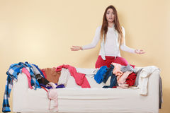 Helpless woman sitting on sofa in messy room home. Helpless woman standing behind on sofa couch in messy living room shrugging. Young girl surrounded by many Royalty Free Stock Photography