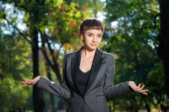 Helpless young business woman shrugs her shoulders Stock Photo