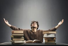 Helpless young man sitting at the desk full of books. Young man sitting in front of desk full of book, spreading his hands helplessly. College student concept Stock Photography