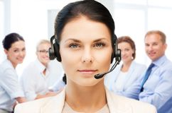 Helpline operator with headphones in call centre. Business and technology concept - helpline operator with headphones in call centre Stock Images