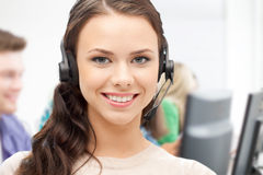 Helpline operator with headphones in call centre Stock Photo