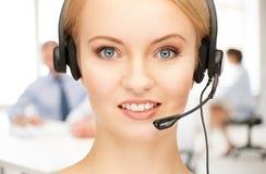 Helpline operator with headphones in call centre. Friendly female helpline operator with headphones in call centre Stock Image