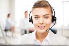 Helpline operator with headphones in call centre. Friendly female helpline operator with headphones in call centre Stock Images