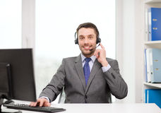 Helpline operator with headphones and computer Royalty Free Stock Photo