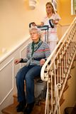 Helps senior old disabled woman to climb the stairs with machin royalty free stock photos