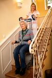 Helps senior old disabled woman to climb the stairs with machine stock photos