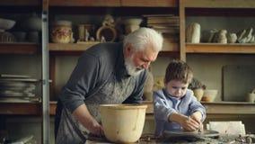 Helpt de hogere volwassene van de aardewerkleraar jonge student om pot van stuk van klei op werpen-wiel te vormen De leuke jongen stock footage