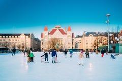Helsínquia, Finlandia Crianças que patinam na pista no quadrado Railway no fundo do teatro nacional finlandês no inverno foto de stock