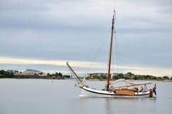 HELSÍNQUIA/FINLANDIA - 27 de julho de 2013: O barco de navigação pequeno é ilha de cruzamento do arround perto do porto de Helsín Foto de Stock Royalty Free