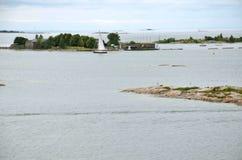 HELSÍNQUIA/FINLANDIA - 27 de julho de 2013: O navio de navigação está cruzando entre ilhas pequenas perto do porto de Helsínquia Fotografia de Stock Royalty Free