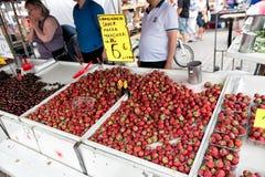 HELSÍNQUIA, FINLANDIA - 23 DE JULHO DE 2016: Os povos compram morangos frescas no mercado no centro de Helsínquia Imagem de Stock