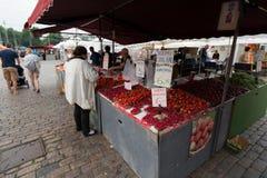HELSÍNQUIA, FINLANDIA - 23 DE JULHO DE 2016: Os povos compram morangos frescas no mercado no centro de Helsínquia Imagem de Stock Royalty Free
