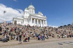 HELSINGFORS FINLAND - JUNI 10, 2017: Folket sitter framme av St-Ni Arkivbilder