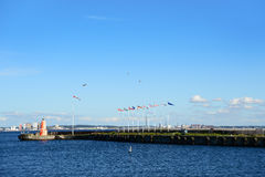 Helsingor, Denmark - July 19, 2016: Lighthouse and flags of European countries in the seaport between Helsingor and Helsingborg. Clear sky above the port in Stock Photos