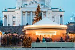 Helsinki, Finland De Kerstmismarkt op Senaatsvierkant met Vakantiecarrousel en Beroemd Oriëntatiepunt is Lutheran Kathedraal en stock foto's