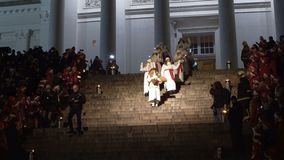 The traditional celebration of Saint Lucia before Christmas. HELSINKI, FINLAND - DECEMBER 13, 2016: Saint Lucia descends the steps of the Cathedral. The stock footage