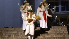 The traditional celebration of Saint Lucia before Christmas. HELSINKI, FINLAND - DECEMBER 13, 2016: Saint Lucia descends the steps of the Cathedral. The stock video footage