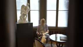 Young woman reading guidebook in the Sinebrychoff Art Museum in Helsinki, Finland. stock footage