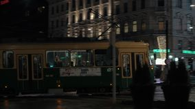 Tram moving in night street of Helsinki, Finland. HELSINKI, FINLAND - JANUARY 07, 2017: Camera following the tram passing by Stockmann shopping center and moving stock video footage