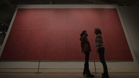 Art museum visitors looking at red polka painting by Yayoi Kusama