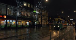 Tramways and walking people in evening Helsinki, Finland. HELSINKI, FINLAND - JANUARY 07, 2017: People walking and tramways running in the evening city. Street stock video