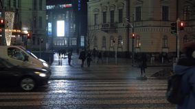 Night street with transport and people traffic. Helsinki, Finland. HELSINKI, FINLAND - JANUARY 07, 2017: Trams and cars traffic on wet paved street at night stock video footage