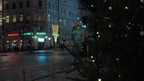 Tramway passing by in night city. Helsinki, Finland. HELSINKI, FINLAND - JANUARY 07, 2017: Tramway passing by with following view to night street and focus on stock video footage