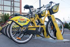 Yellow bicycles for rent stand at row on the pavement. HELSINKI, FINLAND, JUL 03 2017, New yellow bicycles for rent stand at row on the pavement. Bike urban Royalty Free Stock Images