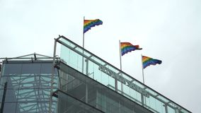 Rainbow flags in support of equality on the roof of a skyscraper in the city centre. HELSINKI, FINLAND - JULY 01, 2017: Rainbow flags in support of equality on stock video
