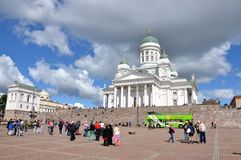 HELSINKI / FINLAND - July 20, 2013: White Helsinki Cathedral, the evangelical lutheran church. At the picture are many people and. Green tourist bus. The Stock Photo