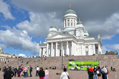 HELSINKI / FINLAND - July 20, 2013: White Helsinki Cathedral, the evangelical lutheran church. At the picture are many people and. Green tourist bus Stock Photo