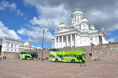 HELSINKI / FINLAND - July 20, 2013: White Helsinki Cathedral, the evangelical lutheran church. At the picture are many people and. Green tourist buses Royalty Free Stock Photo