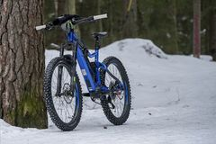 Helsinki, Finland - March 13, 2019: Electric mountain bike standing against tree on snowy ground in Helsinki stock image