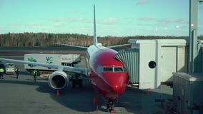 HELSINKI, FINLAND - MARCH 24, 2019: Modern passenger airplane parked to terminal building gate at airside apron of. Airport terminal stock video footage