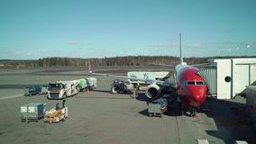 HELSINKI, FINLAND - MARCH 24, 2019: Modern passenger airplane parked to terminal building gate at airside apron of. Airport terminal stock footage