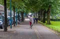 Helsinki, Finland - September 4, 2018. A woman riding a bicycle in a raincoat, pink breeches and a protective helmet. In the park. On the way to two men in royalty free stock images