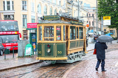 Helsinki, Finlande - tram de touristes guidé 12 juin 2014, de vintage au centre de la ville et le piéton avec le parapluie sous l Image libre de droits
