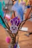 Helsinki, Finlandia - 25 de marzo de 2018: Conejito de pascua en la ramita de Pascua con las plumas coloridas foto de archivo libre de regalías