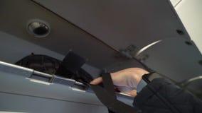 HELSINKI, FINLANDIA - 4 MAGGIO 2019: Il giovane ha messo il suo bagaglio allo scaffale in aeroplano stock footage